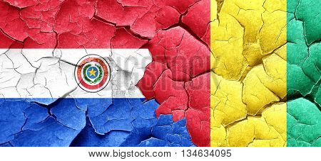 Paraguay flag with Guinea flag on a grunge cracked wall