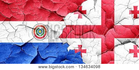 Paraguay flag with Georgia flag on a grunge cracked wall