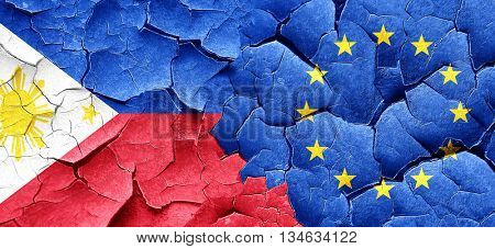 Philippines flag with european union flag on a grunge cracked wa