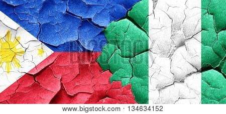 Philippines flag with Nigeria flag on a grunge cracked wall