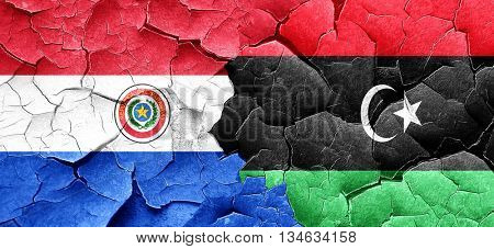 Paraguay flag with Libya flag on a grunge cracked wall