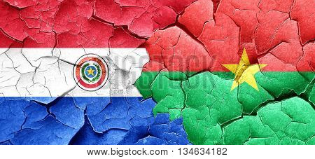 Paraguay flag with Burkina Faso flag on a grunge cracked wall