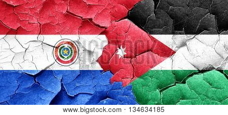 Paraguay flag with Jordan flag on a grunge cracked wall
