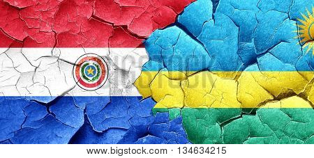 Paraguay flag with rwanda flag on a grunge cracked wall