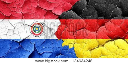Paraguay flag with Germany flag on a grunge cracked wall