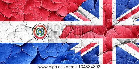 Paraguay flag with Great Britain flag on a grunge cracked wall