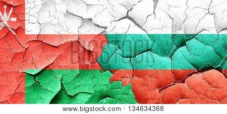 Oman flag with Bulgaria flag on a grunge cracked wall