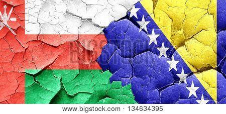 Oman flag with Bosnia and Herzegovina flag on a grunge cracked w