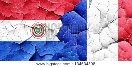 Paraguay flag with France flag on a grunge cracked wall
