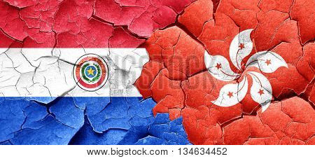 Paraguay flag with Hong Kong flag on a grunge cracked wall
