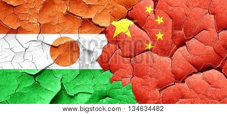 niger flag with China flag on a grunge cracked wall