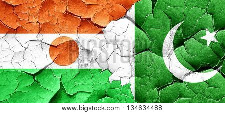 niger flag with Pakistan flag on a grunge cracked wall