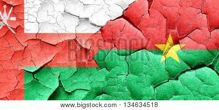 Oman flag with Burkina Faso flag on a grunge cracked wall
