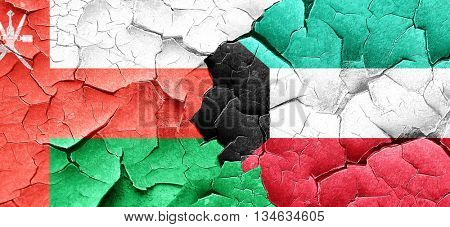 Oman flag with Kuwait flag on a grunge cracked wall