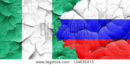 Nigeria flag with Russia flag on a grunge cracked wall