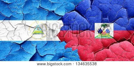 nicaragua flag with Haiti flag on a grunge cracked wall