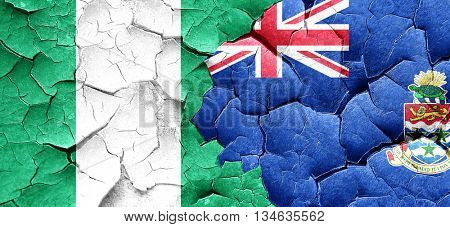 Nigeria flag with Cayman islands flag on a grunge cracked wall