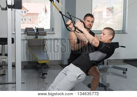 Personal Trainer Helping Man On Trx Fitness Straps