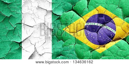 Nigeria flag with Brazil flag on a grunge cracked wall