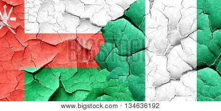 Oman flag with Nigeria flag on a grunge cracked wall