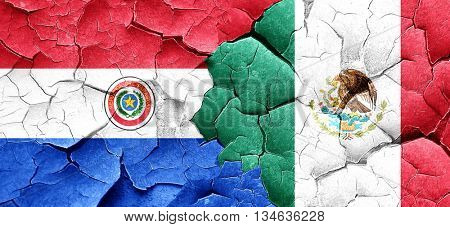 Paraguay flag with Mexico flag on a grunge cracked wall