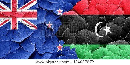 New zealand flag with Libya flag on a grunge cracked wall