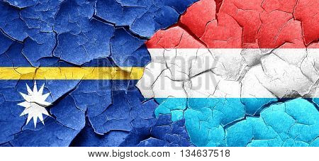 Nauru flag with Luxembourg flag on a grunge cracked wall