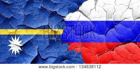 Nauru flag with Russia flag on a grunge cracked wall