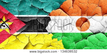 Mozambique flag with Niger flag on a grunge cracked wall