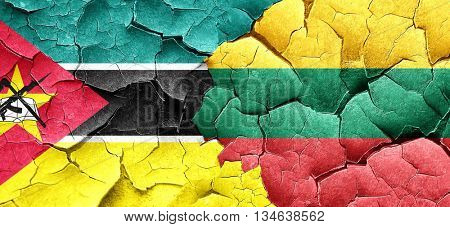 Mozambique flag with Lithuania flag on a grunge cracked wall
