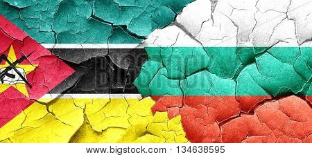 Mozambique flag with Bulgaria flag on a grunge cracked wall