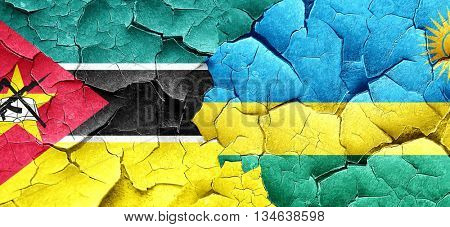 Mozambique flag with rwanda flag on a grunge cracked wall
