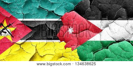 Mozambique flag with Jordan flag on a grunge cracked wall