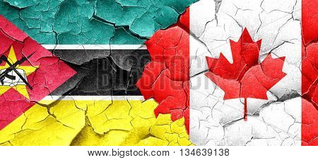 Mozambique flag with Canada flag on a grunge cracked wall