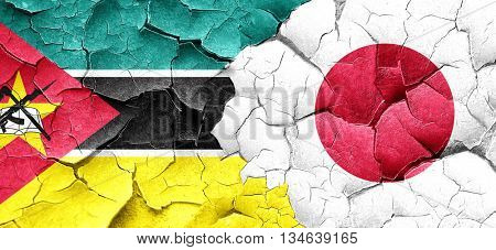 Mozambique flag with Japan flag on a grunge cracked wall