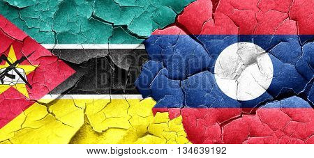 Mozambique flag with Laos flag on a grunge cracked wall
