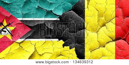 Mozambique flag with Belgium flag on a grunge cracked wall