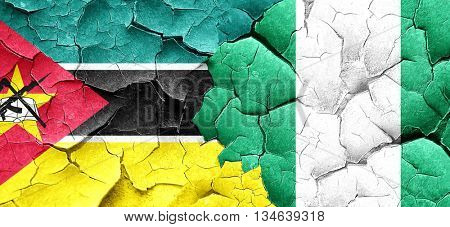 Mozambique flag with Nigeria flag on a grunge cracked wall