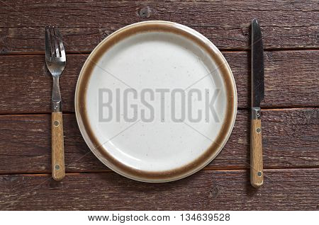Empty plate fork and table knife on old wooden table top view