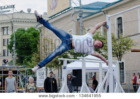 Kharkiv Ukraine - June 11 2016: Young man showing workout exercises outdoors in the street workout competition in Kharkiv on the central square