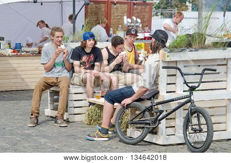 KHARKOV UKRAINE - JUNE 12 2016: A group of teenagers eating junk food in a street food area