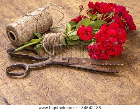 Bouquet Of Red Roses, Ball Of Twine And Old Rusty Scissors On Wooden Table