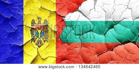Moldova flag with Bulgaria flag on a grunge cracked wall