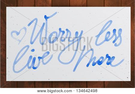 Worry less live more watercolor lettering on wooden background