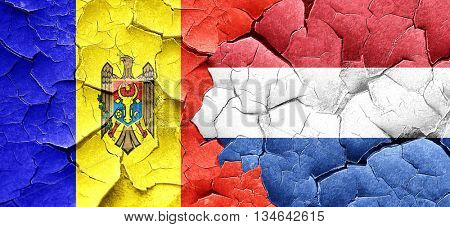 Moldova flag with Netherlands flag on a grunge cracked wall