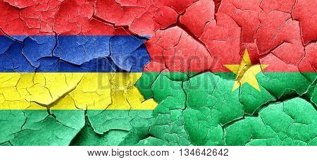 Mauritius flag with Burkina Faso flag on a grunge cracked wall