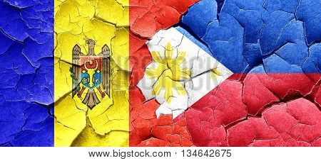 Moldova flag with Philippines flag on a grunge cracked wall