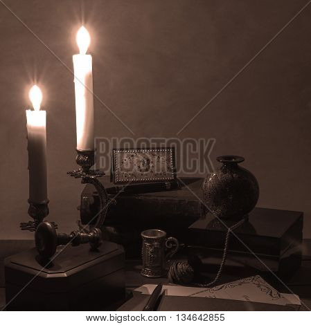 Objects on a table in the candlelight (vintage, sepia)