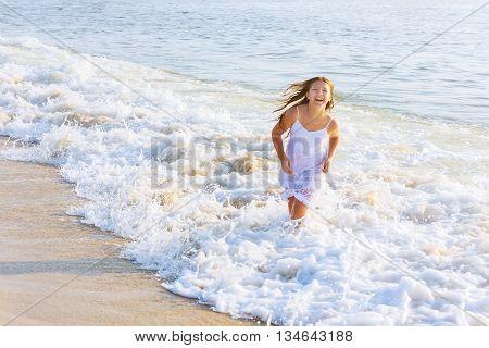 beautiful blonde teenage girl wearing flowy white dress standing ankle dee in ocean water