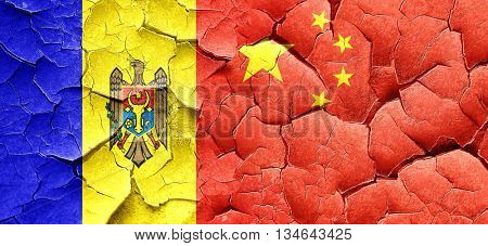 Moldova flag with China flag on a grunge cracked wall
